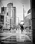 Woman with umbrella on wet and windy day downtown Dayton Ohio. Black and white