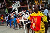 An Afro-Colombian video journalist covers a parade of the Roma neighborhood during the San Pacho festival in Quibdó, Colombia, 28 September 2019. Every year at the turn of September and October, the capital of the Pacific region of Chocó holds the celebrations in honor of Saint Francis of Assisi (locally named as San Pacho), recognized as Intangible Cultural Heritage by UNESCO. Each day carnival groups, wearing bright colorful costumes and representing each neighborhood, dance throughout the city, supported by brass bands playing live music. The festival culminates in a traditional boat ride on the Atrato River, followed by massive religious processions, which accent the pillars of Afro-Colombian's identity – the Catholic devotion grown from African roots.