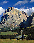 Italy, South Tyrol, Alto Adige, Dolomites, Alpe de Siusi with Sasso Piatto (2.960 m) woman sitting on bench