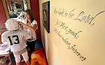 A Bible scripture on the wall serves as a reminder of the blessings in Heather and Brayden Jacobs' lives despite having lost  their husband and father, respectively in a plane crash in 2006.  Heather Jacobs helps her son, Brayden, 11, adjust his helmet while preparing for a night of football before leaving with her five children for a night of activities.  Heather lost her husband, Eric, in a plane crash in 2006 when she was eight months pregnant with their youngest, Ella, and has since been raising her five young children on her own.