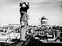 Aircraft spotter on the roof of a building in London. St. Paul's Cathedral is in the background.