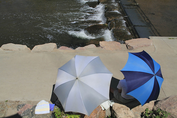 People under umbrellas  along sidewalk and stream, Denver, Colorado, USA.