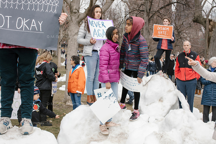 """People gather during the March For Our Lives protest and demonstration in Boston Common in Boston, Massachusetts, USA, on Sat., March 24, 2018. The march was held in response to recent school gun violence. Here, children hold signs reading, """"13 and afraid... not okay,"""" """"Disarm hate,"""" and """"Never again."""""""