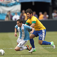 Argentina midfielder Fernando Gago (5) dribbles as Brazil substitute forward Alexandre Pato (19) pressures. In an international friendly (Clash of Titans), Argentina defeated Brazil, 4-3, at MetLife Stadium on June 9, 2012.