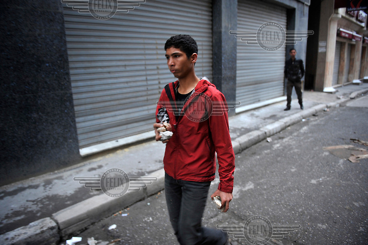 A young man carries stones through the back streets of Tunis. Protests against former prime minister Mohamed Ghannouchi, who took control after the ousting of president Zine El Abidine Ben Ali, turned violent and left at least one dead and several wounded as soldiers used live ammunition and teargas against the protesters..