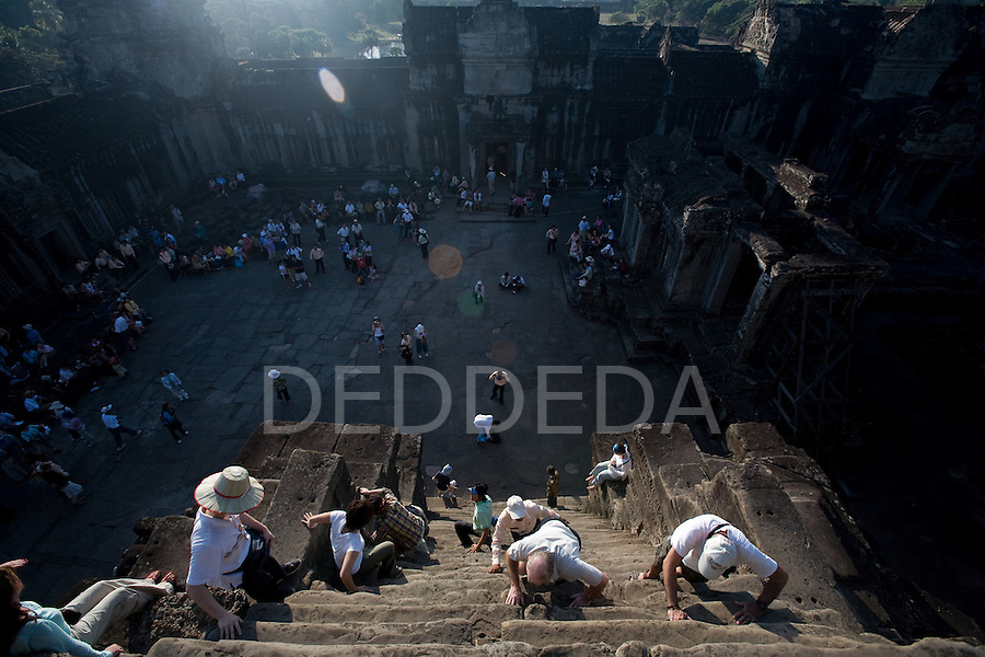 Tourists climb the stairs inside the ancient temple of Angkor Wat, in northwestern Cambodia, near Siem Reap.