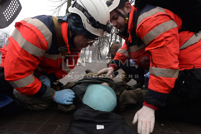Red Cross Medics aid and treat bullet wounded protesters that fell on the field.  Kiev, Ukraine