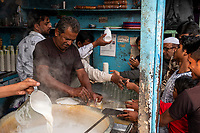 People crowd around Ustad Teapoint, a tea seller a corner of the street market on Meena Bazar in the Chadni Chowk area of Delhi, India, on Tue., Dec. 11, 2018.