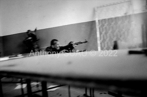 Sukhumi, Abkhazia<br /> September 27, 1993<br /> <br /> From a schoolhouse, a Polish professional soldier (center) and an Abkhazian commander run towards the Parliament hoping to place an Abkhazian flag atop. Hundreds of Abkhazian separatists open fire on Georgian forces held up inside. They do not succeed and are repulsed back into the schoolhouse. Within hours the Abkhazian separatists control the Parliament building and the city --sending thousands fleeing southward into the mountains as refugees.