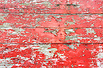 Peeling red paint on old weathered boards.