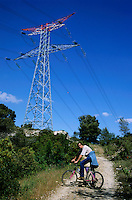 Man waiting on his bicycle near an electrical pylon for his friends to catch up.