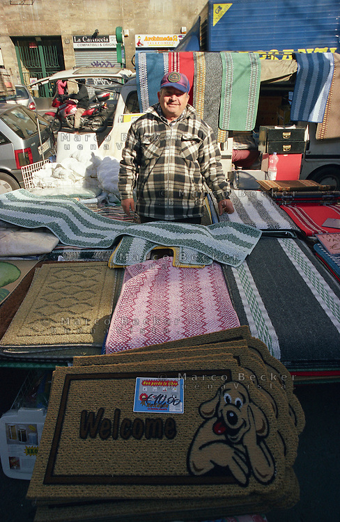 Milano, mercato rionale di viale Papiniano. Venditore di tappetini e zerbini --- Milan, local market in Papiniano street. Seller of mats and doormats