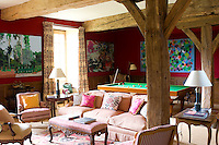This informal living room incorporates a snooker table and is is dominated by massive beams offset by more elegant 18th century furniture and contemporary paintings