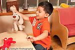 Preschool Headstart 3-5 year olds boy playing with stuffed animal talking to self horizontal