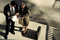Man and woman discussing business; looking over documents. High view. Professionals. Lawyers. Businesswoman. Businessman. Denver Colorado USA.
