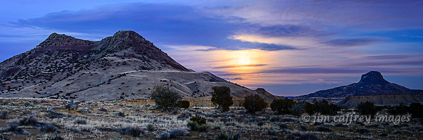 Cerro Cuate and Cabezon Peak in the Rio Puerco Valley of north-central New Mexico with a full moon rising, partially obscured by clouds.