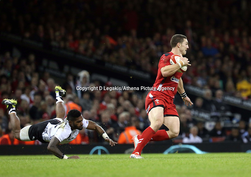 Pictured: George North of Wales (R) avoids a tackle by Masi Matatigo of Fiji (L). Saturday 15 November 2014<br /> Re: Dove Men Series rugby, Wales v Fiji at the Millennium Stadium, Cardiff, south Wales, UK.