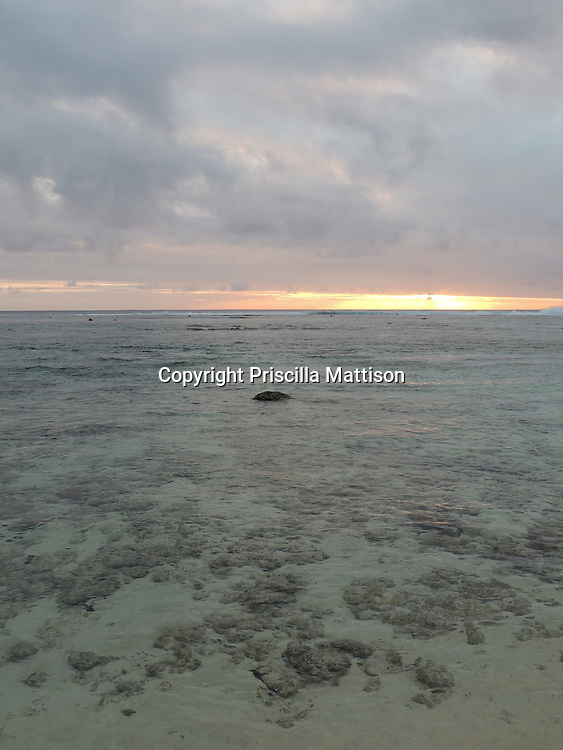Rarotonga, Cook Islands - September 20, 2012:  A band of sunlight remains between lavender clouds and the clear waters of the lagoon.
