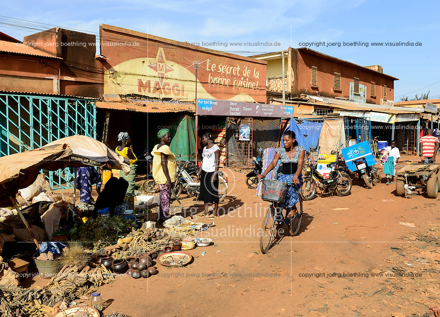 BURKINA FASO , Boulkiemdé Province, Koudougou, shop with Maggi advertisement, Maggi is a brand of swiss Nestle company, selling of natural roots and herbs on the road