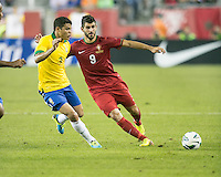 Brazil defender Thiago Silva (3) moves to tackle Portugal forward Nelson Oliveira (9).  In an International friendly match Brazil defeated Portugal, 3-1, at Gillette Stadium on Sep 10, 2013.