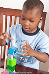 3 year old boy at home playing with blocks and spindle toy vertical