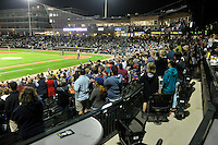 """Fans of the Columbia Fireflies applaud the singing of """"God Bless America"""" in the home opener against the Greenville Drive on Thursday, April 14, 2016, the team's first day at the new Spirit Communications Park in Columbia, South Carolina. The Mets affiliate moved to Columbia this year from Savannah. Columbia won, 4-1. (Tom Priddy/Four Seam Images)"""