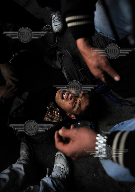 A young protester lies on the pavement, wounded by a bullet in his wrist. Protests against former prime minister Mohamed Ghannouchi, who took control after the ousting of president Zine El Abidine Ben Ali, turned violent and left at least one dead and several wounded as soldiers used live ammunition and teargas against the protesters..