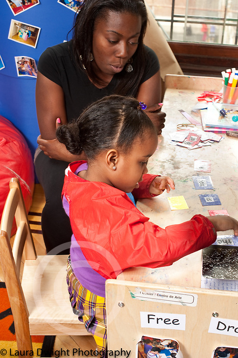 Education preschool 3-4 year olds female teacher working with girl on academic skills identifying words on cards