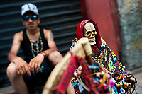 A Mexican follower of Santa Muerte (Saint Death) sits on the street during a religious pilgrimage in Tepito, a rough district of Mexico City, Mexico, 1 May 2011. The religious cult of Santa Muerte is a syncretic fusion of Aztec death worship rituals and Catholic beliefs. Born in lower-class neighborhoods of Mexico City, it has always been closely associated with crime. In the past decades, original Santa Muerte's followers (such as prostitutes, pickpockets and street drug traffickers) have merged with thousands of ordinary Mexican Catholics. The Saint Death veneration, offering a spiritual way out of hardship in the modern society, has rapidly expanded. Although the Catholic Church considers the Santa Muerte's followers as devil worshippers, on the first day of every month, crowds of believers in Saint Death fill the streets of Tepito. Holding skeletal figurines of Holy Death clothed in a long robe, they pray for power healing, protection and favors and make petitions to 'La Santísima Muerte', who reputedly can make life-saving miracles.