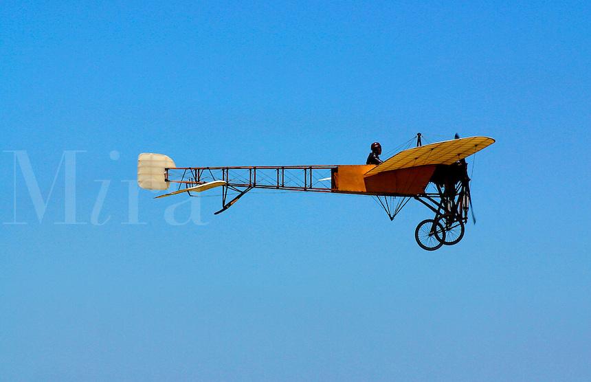 A replica of an antique French airplane flies through a clear blue sky