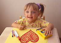 A young girl coloring with crayons.