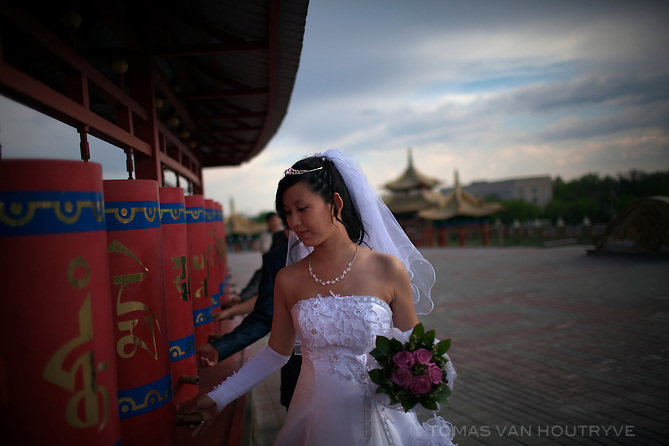 A newlywed bride turns prayer wheels at the main Buddhist temple in Elista, Republic of Kalmykia, Russian Federation on May 7, 2010.