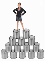 Businesswoman standing on top of cans pyramid (Licence this image exclusively with Getty: http://www.gettyimages.com/detail/103732090 )