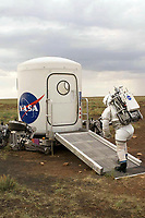 """JSC2006-E-39964 (4-15 Sept. 2006) --- Testing the next generation of spacesuits and equipment in the Arizona desert, an """"astronaut"""" heads to a mock way station that has been delivered to the site by a giant robot capable of """"walking"""" over steep terrain. The giant robot, known as Athlete or All-Terrain Hex-Legged Extra-Terrestrial Explorer vehicle, can be seen at rest beneath the way station. The test was part of the 2006 NASA's Desert Research and Technology Studies (RATS), a team of scientists and engineers who test futuristic equipment that may one day be used for explorations of the moon and Mars."""