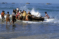 People holding a traditional catamaran fishing boat filled with fresh fish, Colva Beach, Goa, India.