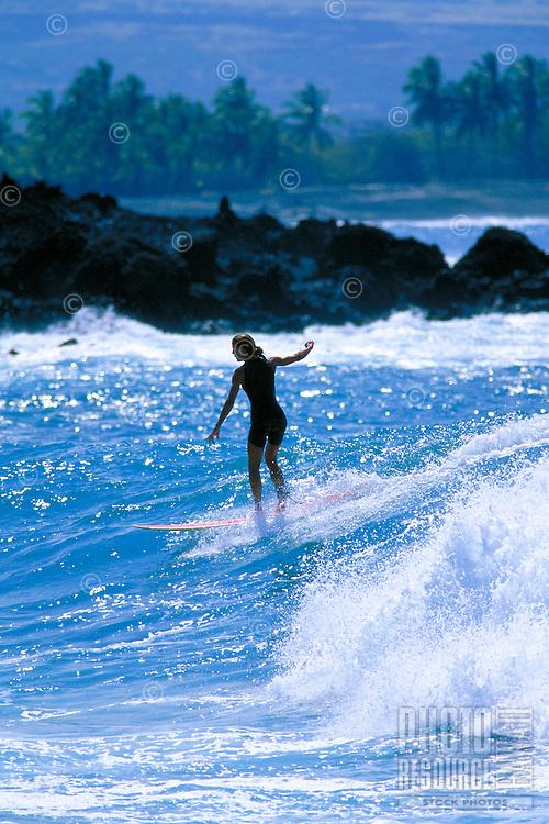 Woman surfing at Pueo Bay, on the Big Island of Hawaii.