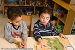 Preschool 4-5 year olds two boys sitting at table looking at picture book talking horizontal