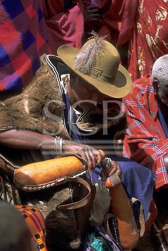 Lolgorian, Kenya. Siria Maasai chief pouring milk from one gourd to another. Cucurbitaceae; Lagenaria siceraria.