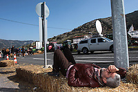 Pictured: A man rests on hay at the road block Tuesday 23 February 2016<br /> Re: Migrants on their way back to Athens have been caught by the blocked off motorway at Tembi, where local farmers have closed off the road, protesting against pension and welfare reforms near Trikala, Greece.