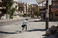 A boy runs for cover across a street exposed to active Syrian Army snipers near a rebel Free Syrian Army (FSA) position close to the front lines of Salaheddin in Aleppo.