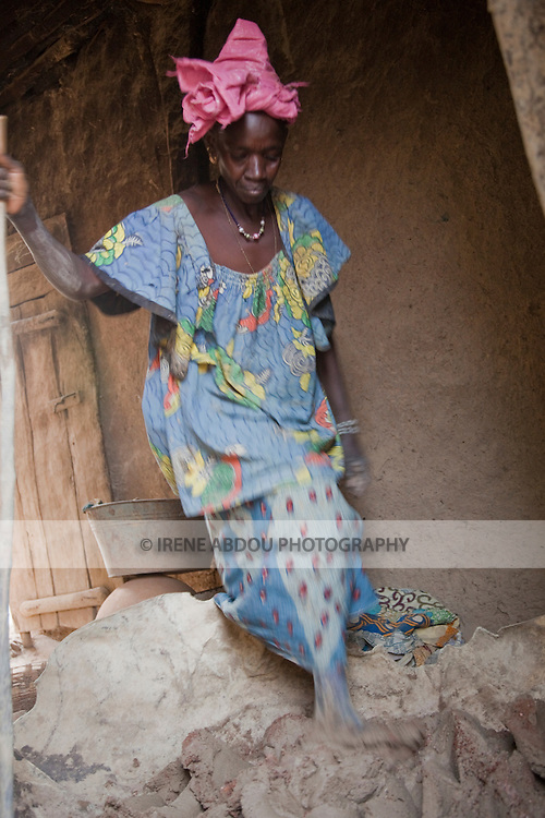 A woman mixes small pieces of fired clay (grog) with clay body by stamping on it.  Mixing grog with the clay body will help the pot withstand the firing and repeated thermal stress of cooking.  In the village of Kalabougou near Segou, Mali, women of the numu blacksmiths population have worked for centuries as traditional potters.  A 7-day fabrication cycle leads to the weekly Saturday afternoon firing of the kilns, in which large stacks of pots are covered with grass and set on fire.