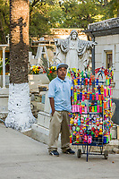 Matatlan, Oaxaca; Mexico; North America.  Day of the Dead Celebration.  Indian Vendor Selling Refreshments and Decorations in the San Miguel Cemetery.