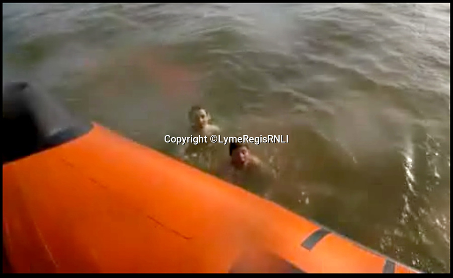 BNPS.co.uk (01202 558833)<br /> Pic : LymeRegisRNLI/BNPS<br /> <br /> The lifeboat crew approach the two boys in the water.<br /> <br /> This is the dramatic moment two teenage tombstoners were saved from drowning after they were swept 250 yards out to sea.<br /> <br /> Archie Woollacott, 14, got dragged away by a strong current after plunging off a harbour wall at Axmouth, Devon. His friend Bozhidrar Bobev jumped in to rescue him but was also taken out to sea.<br /> <br /> The stricken pair spent an hour treading water before they were spotted by the Lyme Regis lifeboat crew in the nick of time.<br /> <br /> The next day Archie visited to RNLI station to thank the crew by baking them a lemon drizzle cake.