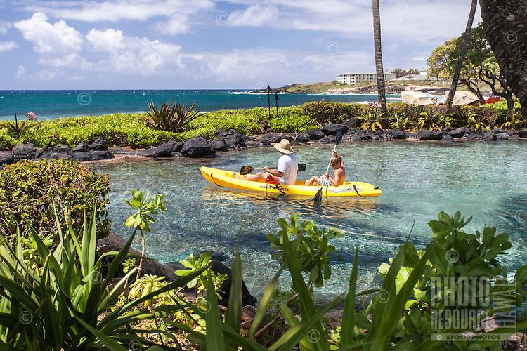 Caucasian man and boy kayaking in lagoon at Grand Hyatt Kaua'i Resort in Koloa, Kaua'i