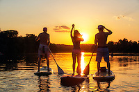 A group of friends, silhouetted by the sunset, reflect the fit Austin Lifestyle by exercising on stand-up paddle boards at sunset on Lady Bird Lake in Austin, Texas.