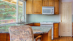 Residential kitchen.  Circa 1990.  Empty.  Oak and granit.  Clean, light, open kitchen.