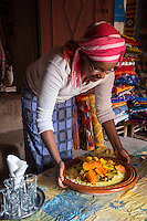 Morocco.  Woman of African-Berber Ethnicity Bringing Couscous to the Table. Ait Benhaddou Ksar, a World Heritage Site.