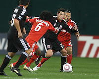 Branko Boskovic #27 of D.C. United slips a pass between Julian de Guzman #6 and Dwayne De Rosario #14 of Toronto FC during an MLS match that was the final appearance of D.C. United's Jaime Moreno at RFK Stadium, in Washington D.C. on October 23, 2010. Toronto won 3-2.