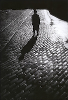 Silhouetted man on cobblestones<br />