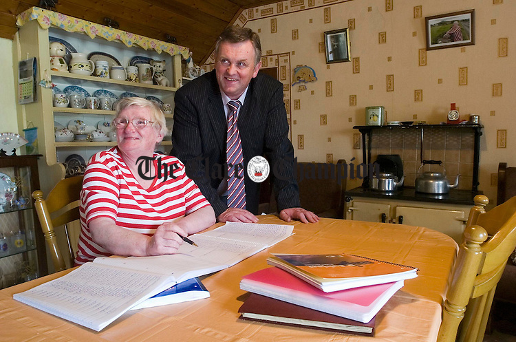 Rose Glynn of Aughinish working on the parish records as the Rural Social Scheme co-ordinator Ger Kennedy drops in. Photograph by John Kelly.